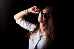 The cool girl in black sunglasses. Portrait of pretty young woman with long curly wavy brown hair on the black background royalty free stock images