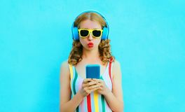 cool girl blowing red lips holding phone listening to music in wireless headphones on colorful blue royalty free stock image