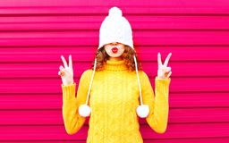 Cool girl blowing red lips makes air kiss wearing colorful knitted hat, yellow sweater royalty free stock photography