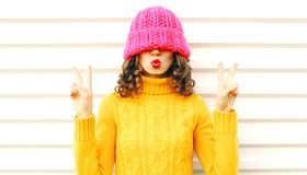Cool girl blowing red lips makes air kiss wearing colorful knitted pink hat, yellow sweater royalty free stock photography