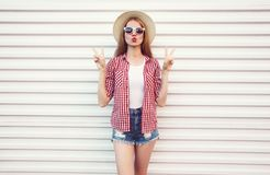 Cool girl blowing red lips sending sweet air kiss in summer round straw hat, checkered shirt, shorts on white wall. Background royalty free stock images