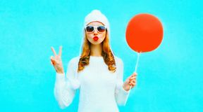 cool girl blowing red lips sends an air kiss, holding red air balloon stock images