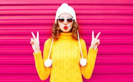 Cool girl blowing red lips wearing a colorful knitted yellow sweater hat stock image