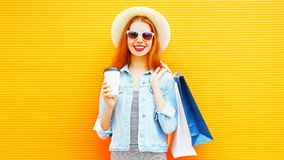 Cool girl with a coffee cup, shopping bags, straw hat on orange Stock Image
