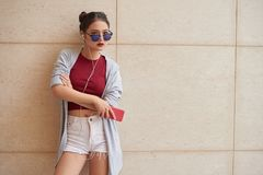 Cool girl. Cool young Vietnamese woman in sunglasses standing at the wall stock image