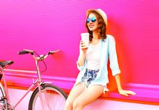 Cool girl drinks coffee of cup near retro vintage pink bicycle. Over colorful pink background stock photography