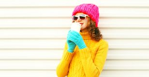 Cool girl drinks coffee from cup wearing knitted colorful pink hat yellow sweat stock image