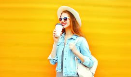 Cool girl drinks a coffee on orange background Royalty Free Stock Photos