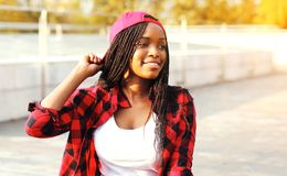 Cool girl having fun in the city park, wearing a red checkered shirt. And cap sitting stock photo