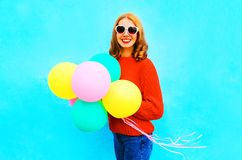Cool girl holds a colorful air balloons on blue Stock Photos