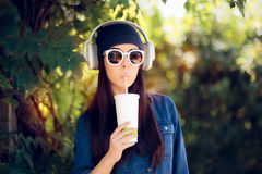 Cool Girl in Jeans Outfit Wearing Sunglasses Drinking Juice and Listening to Music Royalty Free Stock Photos