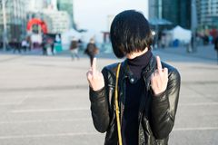 Cool girl in leather jacket show middle finger Stock Images