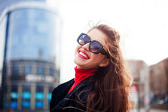 Cool girl with long hairstyle and red lips having fun in the city. She wears sunglasses and smiling to camera with snow-white smil Stock Photo