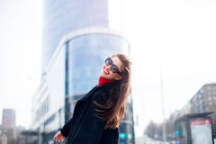 Cool girl with long hairstyle and red lips having fun in the city. She wears sunglasses and smiling to camera with snow-white smil Royalty Free Stock Images