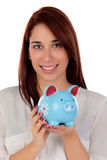 Cool girl looking at camera with a blue moneybox Royalty Free Stock Photography