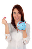 Cool girl looking at camera with a blue moneybox Royalty Free Stock Photo