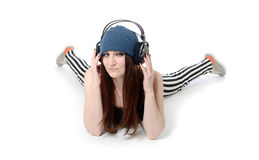 Cool girl lying in headphones on white Royalty Free Stock Photography