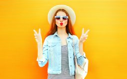 Cool girl make an air kiss on orange background Stock Images