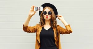 Cool girl model taking photo picture self-portrait on smartphone stock image
