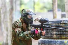 Cool girl with paint gun playing paintball game Royalty Free Stock Image
