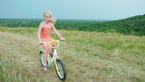 A cool girl in a pink dress rides a bike in the countryside. Carefree childhood in the village. Slow motion 4k video stock video