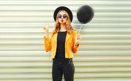 Cool girl posing blowing red lips sends air kiss holding black air balloon royalty free stock photo