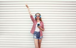 Cool girl raises her hand up in headphones with smartphone listening to music wearing checkered shirt, shorts posing on white wall. Background stock photo