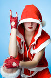 Cool girl in Santa Claus clothes. Over blue background Royalty Free Stock Photo