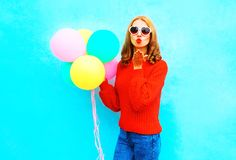 Cool girl sends an air kiss with colorful balloons on a blue Royalty Free Stock Photography
