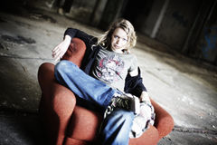 Cool girl sitting in old red sofa Royalty Free Stock Photography