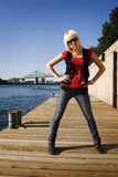 Cool girl standing on dock. With bridge behind Royalty Free Stock Image