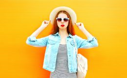 Cool girl in a straw hat on orange background Stock Image