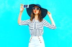Cool girl is taking a picture on a smartphone wearing a straw hat. Cool girl is taking a picture on a smartphone wearing a straw summer hat, white pants over royalty free stock image