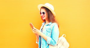 Cool girl is using the smartphone in the city on a orange Stock Image