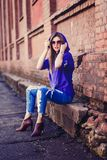 Cool girl wearing jeans and sunglasses. Fashion cool girl wearing jeans and sunglasses, red background Royalty Free Stock Image