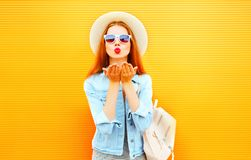 Cool girl young woman sends an air kiss on orange background. Cool girl young woman sends an air kiss on a orange background royalty free stock photo