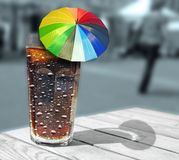 Cool glass cola coke drink with summer parasol umbella stock image