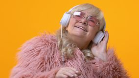 Cool grandmother in white headphones moving to music, pretending be dj, fun. Stock footage stock video footage