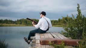 Cool guitarist plays sitting on the pier of the lake. Cinematic shots in motion. It`s very beautiful stock footage