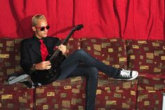 Cool guitarist sitting on red couch. Yong male musician siting on red couch playing guitar Stock Images