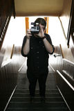 Cool guy. Young college age man wearing glasses standing in stairwell holding polaroid camera taking a picture Royalty Free Stock Photo