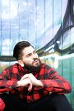 Cool guy with beard and piercings sitting outdoors Royalty Free Stock Photos