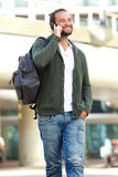 Cool guy with beard smiling outside with mobile phone and bag Royalty Free Stock Image