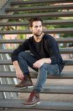 Cool guy in black clothing sitting on steps Royalty Free Stock Photo