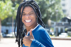 Cool guy with dreadlocks showing thumb in the city Royalty Free Stock Image