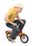 Cool guy goes on a children's bicycle. On white background Royalty Free Stock Images