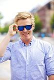 Cool Guy with His Shades On. Portrait of a handsome and cool guy outdoors with his shades on Royalty Free Stock Image