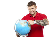 Cool guy holding and pointing at the globe Royalty Free Stock Photo