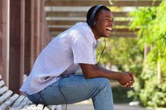 Cool guy laughing with headphones in park Stock Photo