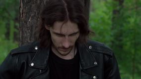 The guy in the leather jacket in the woods. Cool guy in a leather jacket in the woods among the pines stock video